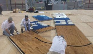 This undated photo provided by Connor Sports Flooring shows workers installing the hardwood floor being used at the Final Four in Arlington, Texas.  Connor has been manufacturing the floors for the Final Four for nearly a decade. It also makes 700 courts each year for the NBA, schools, gyms and colleges. (AP Photo/Connor Sports Flooring)