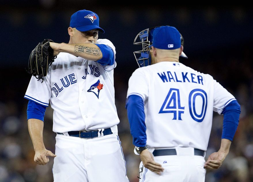 Toronto Blue Jays starting pitcher Dustin McGowan, left, looks on as pitching coach Pete Walker (40) makes a trip to the mound during first inning AL baseball action against the New York Yankees in Toronto on Friday, April 4, 2014.  (AP Photo/The Canadian Press,Peter Power)