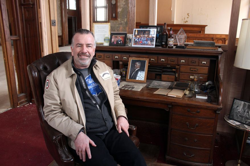 In this March 24, 2014 photo Jim Haertel sits at the desk of Frederick Pabst, who started the Pabst Brewery in 1884, in Milwaukee. He bought the company's former administrative building and another one in 2001. He supports an effort to try to raise money to bring the company's headquarters back to Milwaukee.  (AP Photo/Carrie Antlfinger)