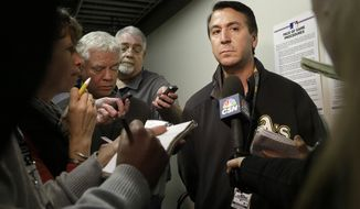 Oakland Athletics vice president of stadium operations Dave Rinetti, right, talks to reporters after a baseball game between the Athletics and the Seattle Mariners was postponed for unplayable field condition, in Oakland, Calif., Friday, April 4, 2014. (AP Photo/Jeff Chiu)
