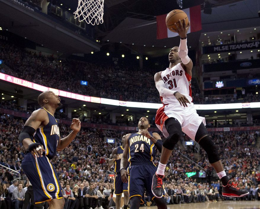 Toronto Raptors guard Terrence Ross (31) soars past Indiana Pacers forwards David West, left, and Paul George (24) during the first half of an NBA basketball game Friday, April 4, 2014, in Toronto. (AP Photo/The Canadian Press, Frank Gunn)