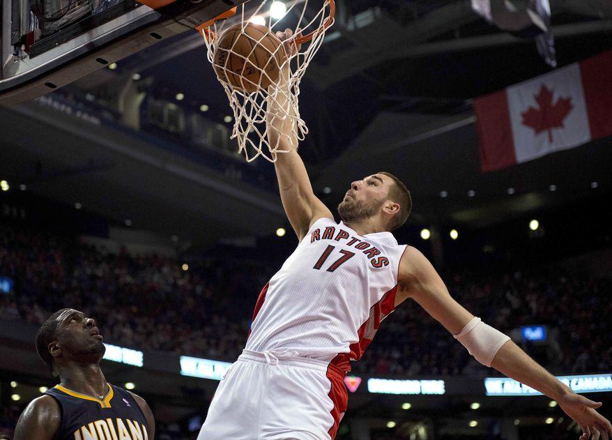 Toronto Raptors center Jonas Valanciunas (17) dunks against Indiana Pacers center Roy Hibbert during the first half of an NBA basketball game Friday, April 4, 2014, in Toronto. (AP Photo/The Canadian Press, Frank Gunn)