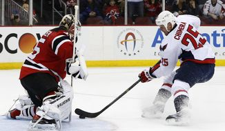 New Jersey Devils goalie Cory Schneider, left, blocks a shot by Washington Capitals left wing Jason Chimera during the first period of an NHL hockey game, Friday, April 4, 2014, in Newark, N.J. (AP Photo/Julio Cortez)