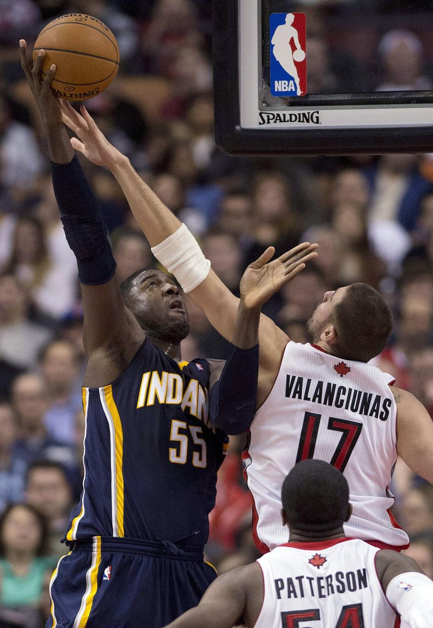 Toronto Raptors center Jonas Valanciunas (17) defends Indiana Pacers center Roy Hibbert during the first half of an NBA basketball game Friday, April 4, 2014, in Toronto. (AP Photo/The Canadian Press, Frank Gunn)