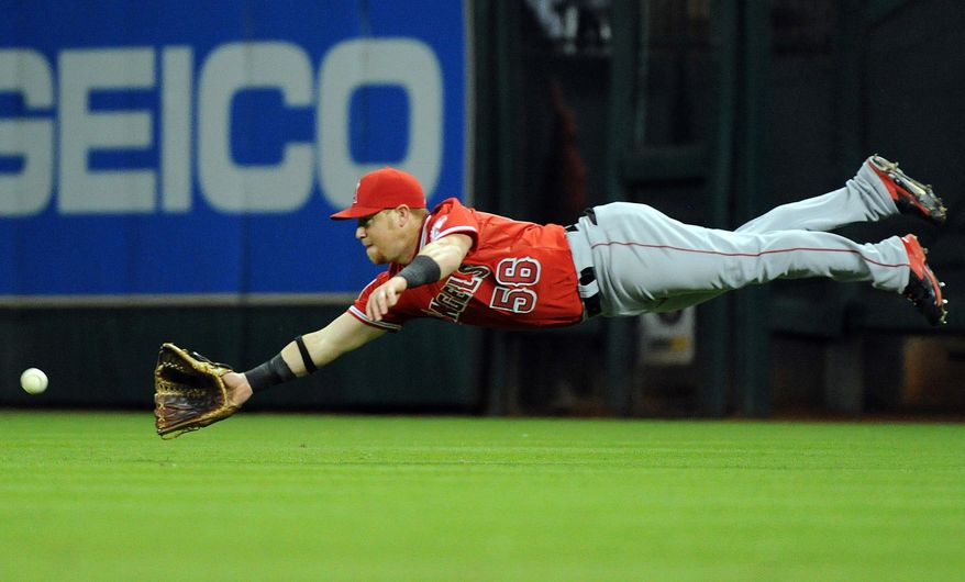 Los Angeles Angels' Kole Calhoun dives but misses catching a line drive hit by Houston Astros' Jose Altuve in the fourth inning of a baseball game on Friday, April 4, 2014, at Minute Maid Park in Houston. (AP Photo/Eric Christian Smith)