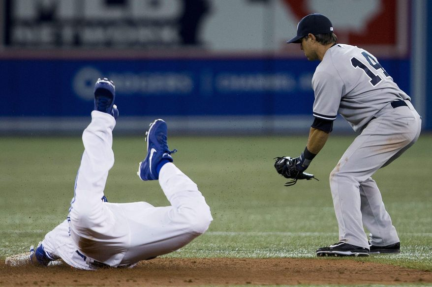 Toronto Blue Jays first baseman Edwin Encarnacion, left, slides safe into second base on a double past New York Yankees second baseman Brian Roberts (14) during third inning AL baseball action in Toronto on Friday, April 4, 2014.   (AP Photo/The Canadian Press,Peter Power)