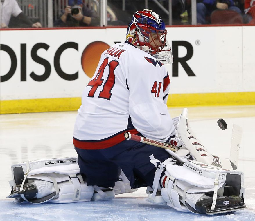 Washington Capitals goalie Jaroslav Halak, of Slovakia, makes a save against the New Jersey Devils during the second period of an NHL hockey game, Friday, April 4, 2014, in Newark, N.J. (AP Photo/Julio Cortez)