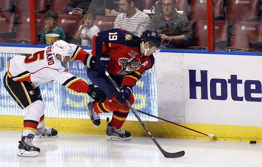 Calgary Flames defenseman Mark Giordano (5) and Florida Panthers right wing Scottie Upshall (19) fight for the puck during the first period of an NHL hockey game in Sunrise, Fla., on Friday, April 4, 2014. (AP Photo/Terry Renna)