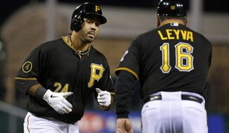 Pittsburgh Pirates' Pedro Alvarez (24) rounds third to greetings from coach Nick Leyva (16) after hitting a solo home run off St. Louis Cardinals starting pitcher Shelby Miller during the second inning of a baseball game in Pittsburgh on Friday, April 4, 2014. (AP Photo/Gene J. Puskar)