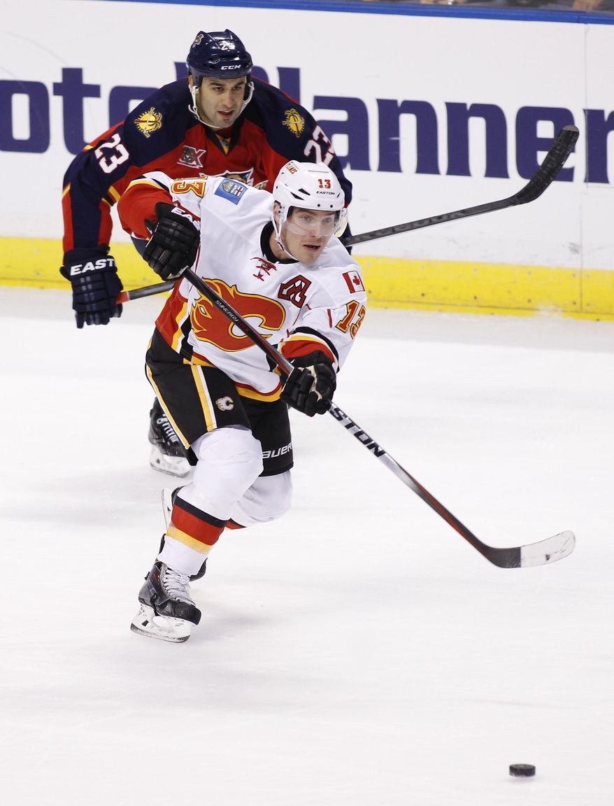 Calgary Flames left wing Mike Cammalleri (13) shoots the puck as Florida Panthers center Scott Gomez (23) follows during the first period of an NHL hockey game in Sunrise, Fla., Friday, April 4, 2014. (AP Photo/Terry Renna)