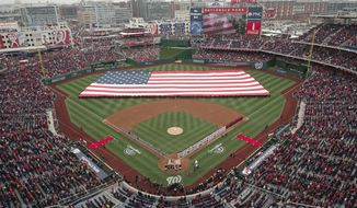 The United States Navy Ceremonial Guard stretches a large U.S. Flag across the field during the playing of the National Anthem before the baseball home opener between the Atlanta Braves and Washington Nationals at Nationals Park Friday, April 4, 2014, in Washington. (AP Photo/J. David Ake)