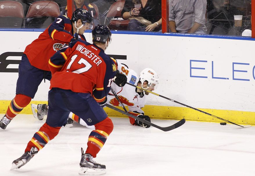 Florida Panthers center Jesse Winchester (17) and defenseman Dmitry Kulikov (7) go after the puck as Calgary Flames left wing T.J. Galiardi (39) falls during the second period of an NHL hockey game in Sunrise, Fla., on Friday, April 4, 2014. (AP Photo/Terry Renna)
