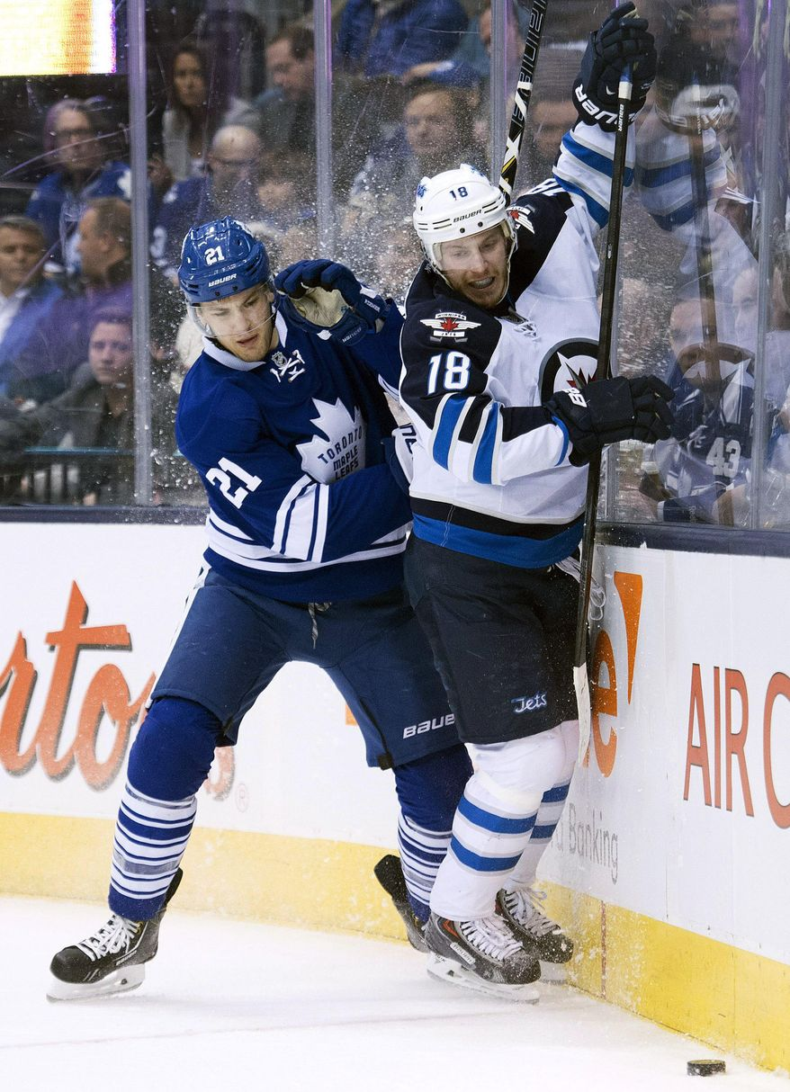 Toronto Maple Leafs forward James van Riemsdyk (21) battles for the puck against Winnipeg Jets forward Bryan Little (18) during first-period NHL hockey game action in Toronto, Saturday, April 5, 2014. (AP Photo/The Canadian Press, Nathan Denette)