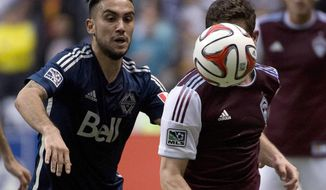 Vancouver Whitecaps FC's Pedro Morales fights for control of the ball with Colorado Rapids FC's Dillon Powers during second half of MLS soccer action in Vancouver, Canada, Saturday, April 5, 2014. (AP Photo/The Canadian Press, Jonathan Hayward)
