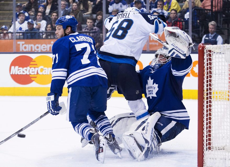 Toronto Maple Leafs goalie James Reimer, right, is knocked over by Winnipeg Jets forward Eric O'Dell, center, and Maple Leafs forward David Clarkson, left, during third-period NHL hockey game action in Toronto, Saturday, April 5, 2014. (AP Photo/The Canadian Press, Nathan Denette)