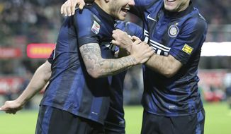 Inter Milan forward Mauro Icardi, left, of Argentina, celebrates with his compatriot teammate Rodrigo Palacio after scoring during the Serie A soccer match between Inter Milan and Bologna at the San Siro stadium in Milan, Italy, Saturday, April 5, 2014. (AP Photo/Antonio Calanni)
