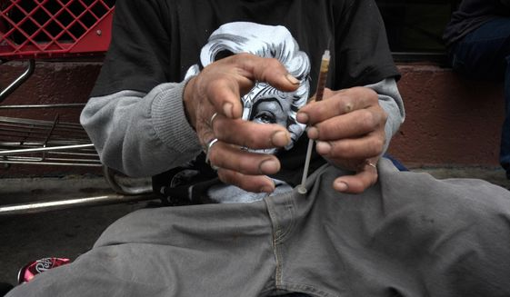 In this Monday, May 6, 2013 file photo, a drug addict prepares a needle to inject himself with heroin in front of a church in the Skid Row area of Los Angeles. In the midst of an opiod epidemic, city officials in Philadelphia are considering establishing safe sites for heroin addicts to inject themselves under doctor supervision. (AP Photo/Jae C. Hong) **FILE**