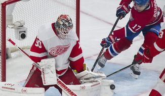 Detroit Red Wings goaltender Jonas Gustavsson is scored on by Montreal Canadiens' Brian Gionta (not shown) as Canadiens' Rene Bourque looks for a rebound during the third period of an NHL hockey game in Montreal, Saturday, April 5, 2014. (AP Photo/The Canadian Press, Graham Hughes)