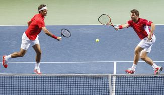 Switzerland's Stanislas Wawrinka, right, watched by his doubles partner Roger Federer, left, left, returns the ball to Kazakhstan's Aleksandr Nedovyesov, and Andrey Golubev, during their doubles match of the tennis Davis Cup World Group quarterfinal match between Switzerland and Kazakhstan,  in Geneva, Switzerland, Saturday, April 5, 2014.(AP Phtoo/Keystone,Salvatore Di Nolfi)