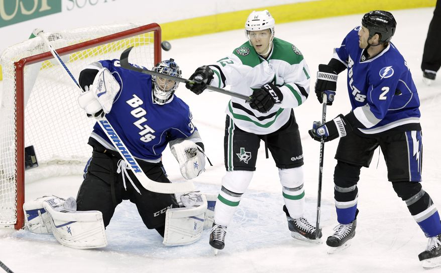Dallas Stars right wing Alex Chiasson (12) reaches out to deflect the puck in front of Tampa Bay Lightning goalie Ben Bishop (30) and defenseman Eric Brewer (2) during the first period of an NHL hockey game on Saturday, April 5, 2014, in Tampa, Fla. (AP Photo/Chris O'Meara)