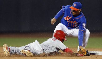 New York Mets shortstop Ruben Tejada (11) tags out Cincinnati Reds Billy Hamilton who was trying to steal second base in the eighth inning of a baseball game at Citi Field in New York, Friday, April 4, 2014. The Mets won 4-3. (AP Photo/Paul J. Bereswill)