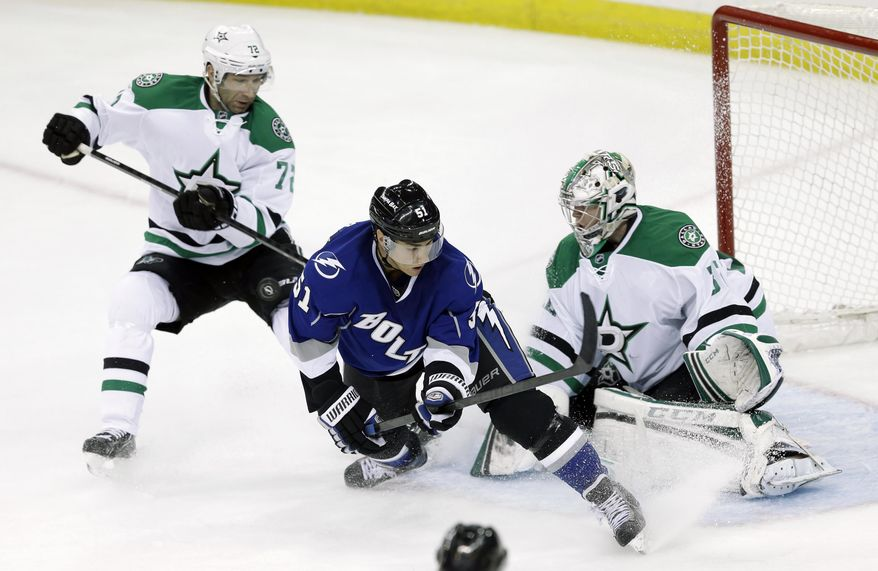 Tampa Bay Lightning center Valtteri Filppula (51), of Finland, puts a backhanded shot against Dallas Stars goalie Kari Lehtonen (32), also of Finland, as Stars right wing Erik Cole (72) defends during the second period of an NHL hockey game on Saturday, April 5, 2014, in Tampa, Fla. (AP Photo/Chris O'Meara)