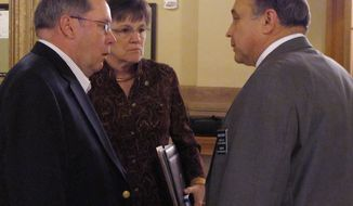 Democratic Kansas legislators confer during a break in negotiations between the House and Senate over school funding legislation, Saturday, April 5, 2014, in a hallway at the Statehouse in Topeka, Kan. They are, left to right, Senate Minority Leader Anthony Hensley, of Topeka; Sen. Laura Kelly, of Topeka, and Rep. Jerry Henry, of Atchison. (AP Photo/John Hanna)