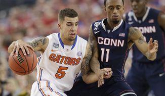 Florida guard Scottie Wilbekin, left, drives past Connecticut guard Ryan Boatright during the first half of an NCAA Final Four tournament college basketball semifinal game Saturday, April 5, 2014, in Arlington, Texas. (AP Photo/David J. Phillip)