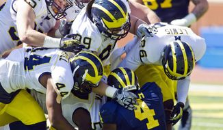 Michigan running back De'Veon Smith (4) is gang-tackled by linebacker Joe Bolden (35), defensive back Delano Hill (44), defensive tackle Matthew Godin (99) and defensive back Jourdan Lewis (26) during the team's annual spring football game, Saturday, April 5, 2014, in Ann Arbor, Mich. (AP Photo/Tony Ding)