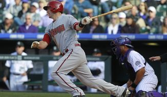 Arizona Diamondbacks' Paul Goldshmidt, left, follows the flight of his RBI-single as Colorado Rockies catcher Wilin Rosario looks on in the eighth inning of the Rockies' 12-2 victory in a baseball game in Denver on Friday, April 4, 2014. (AP Photo/David Zalubowski)