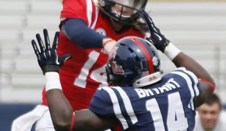 Mississippi quarterback Bo Wallace, top, throws over the defense of linebacker Serderius Bryant (14) during an NCAA college football spring scrimmage on Saturday, April 5, 2014, in Oxford, Miss. (AP Photo/Rogelio V. Solis)