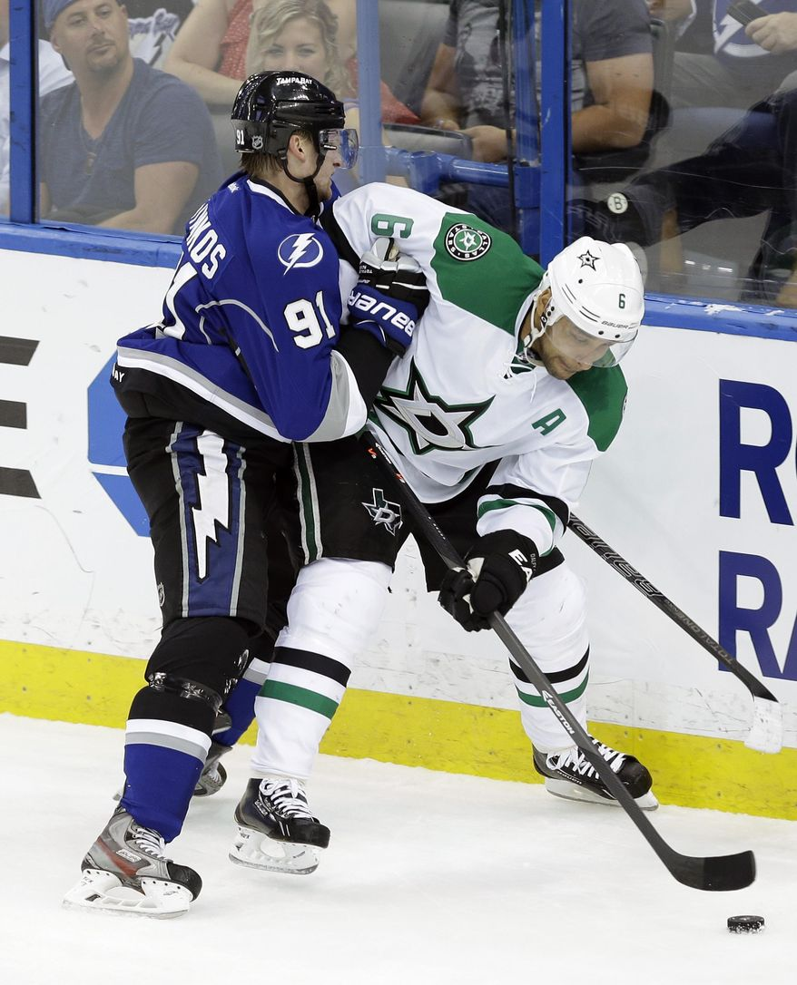 Tampa Bay Lightning center Steven Stamkos (91) pushes Dallas Stars defenseman Trevor Daley (6) into the boards during the first period of an NHL hockey game on Saturday, April 5, 2014, in Tampa, Fla. (AP Photo/Chris O'Meara)