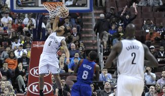 Brooklyn Nets' Deron Williams (8) dunks the ball over Philadelphia 76ers' Tony Wroten during the first half of an NBA basketball game on Saturday, April 5, 2014, in Philadelphia. (AP Photo/Michael Perez)