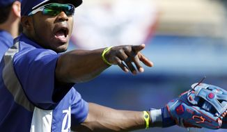 Los Angeles Dodgers' Yasiel Puig makes his point to a teammate during warm ups for a baseball game against the San Francisco Giants on Saturday, April 5, 2014, in Los Angeles. (AP Photo/Alex Gallardo)
