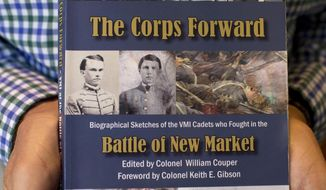 "ADVANCE FOR USE SATUDAY, APRIL 5 - In this photo taken on March 24, 2014, Ken Dice holds a copy of ""The Corps Forward, Battle of New Market,"" at his home in Moneta, Va. Dice is methodically sifting through records to find the living descendants of the Virginia Military Institute cadets who 150 years ago marched in the rain and muck from their Lexington campus to New Market. (AP Photo/The Roanoke Times, Erica Yoon)  LOCAL TV OUT; SALEM TIMES REGISTER OUT; FINCASTLE HERALD OUT;  CHRISTIANBURG NEWS MESSENGER OUT; RADFORD NEWS JOURNAL OUT; ROANOKE STAR SENTINEL OUT"