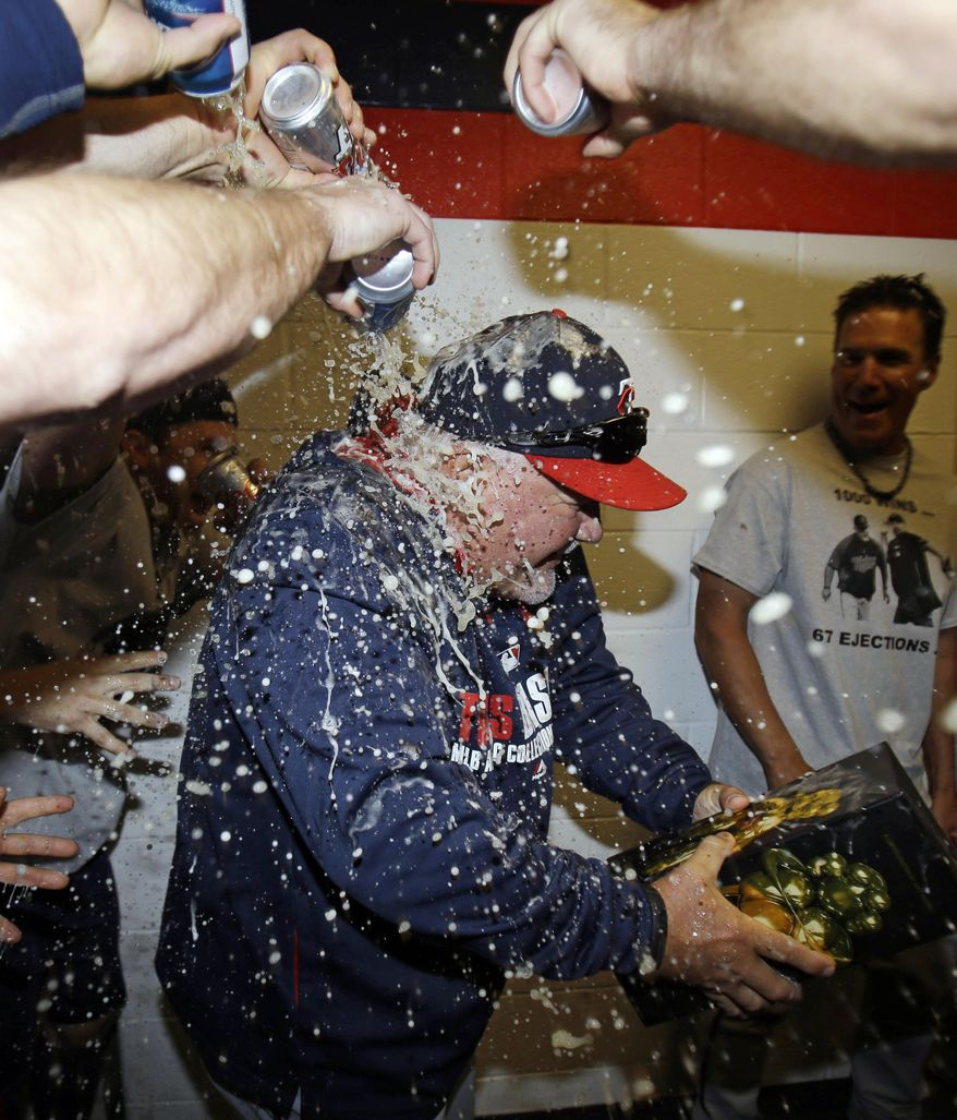 Minnesota Twins manager Ron Gardenhire is doused with beer after the Twins defeated the Cleveland Indians 7-3 in a baseball game, Saturday, April 5, 2014, in Cleveland. The Twins win gives Gardenhire his 1,000th career victory. (AP Photo/Tony Dejak)
