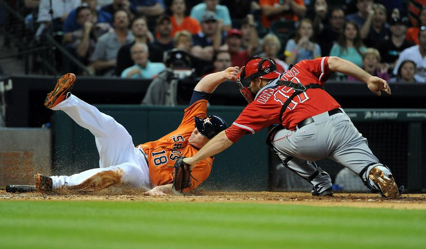 Houston Astros' Marc Krauss, left, is tagged out at home by Los Angeles Angels' Chris Iannetta in the second inning of a baseball game on Friday, April 4, 2014, at Minute Maid Park in Houston. (AP Photo/Eric Christian Smith)