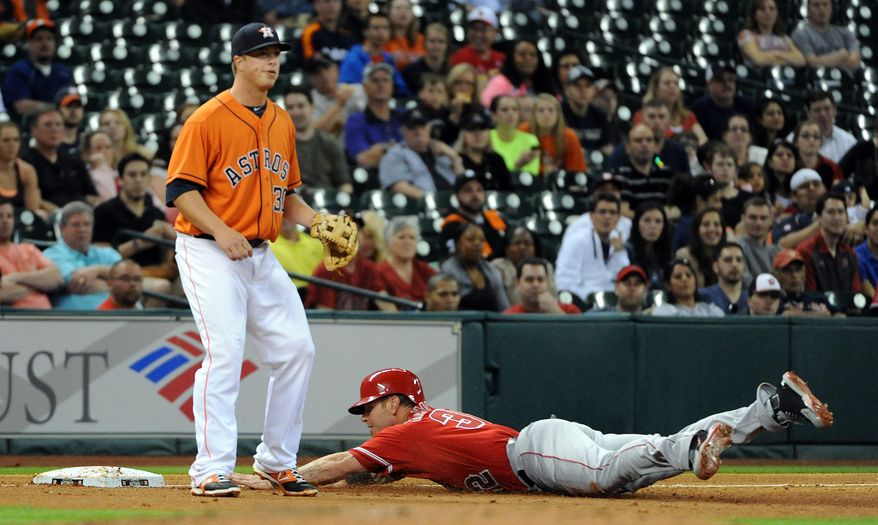 Los Angeles Angles' Josh Hamilton, right, slides into third base past Houston Astros' Matt Dominguez after a David Freese single in the third inning of a baseball game on Friday, April 4, 2014, at Minute Maid Park in Houston. (AP Photo/Eric Christian Smith)