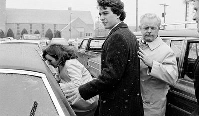 FILE - In this March 17, 1984 file photo, Robert Kennedy Jr. and his wife, Emily, get into a car as they are escorted by private investigator Don Wiley outside the courthouse in Rapid City, S.D. Kennedy received a suspended sentence and two years probation on his guilty plea to a charge of heroin possession. (AP Photo/Mark Elias)