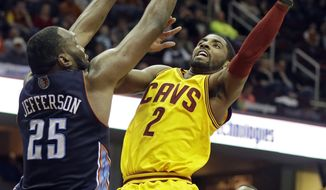Cleveland Cavaliers' Kyrie Irving (2) shoots against Charlotte Bobcats' Al Jefferson (25) in the second quarter of an NBA basketball game on Saturday, April 5, 2014, in Cleveland. (AP Photo/Mark Duncan)