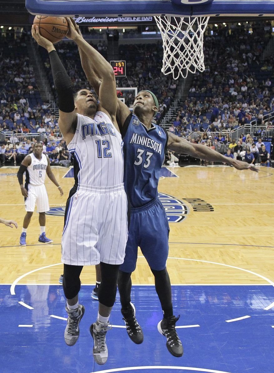 Orlando Magic's Tobias Harris (12) goes up to shoot as he is defend by Minnesota Timberwolves' Dante Cunningham (33) during the first half of an NBA basketball game in Orlando, Fla., Saturday, April 5, 2014. (AP Photo/John Raoux)