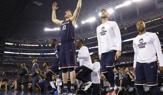 Connecticut forward Tyler Olander (10) celebrates with teammates at the end of an NCAA Final Four tournament college basketball semifinal game against Florida Saturday, April 5, 2014, in Arlington, Texas. Connecticut won 63-53. (AP Photo/Eric Gay)