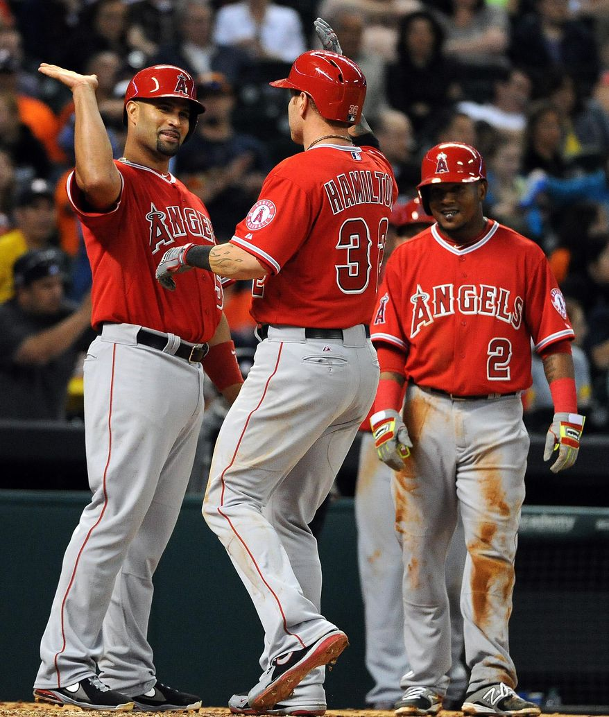 Los Angeles Angels' Josh Hamilton, center, celebrates his three-run home run with teammate Albert Pujols, left, as Erick Aybar (2) looks on in the sixth inning of a baseball game against the Houston Astros, Friday, April 4, 2014, at Minute Maid Park in Houston. (AP Photo/Eric Christian Smith)