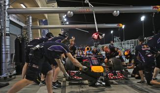 Mechanics prepares the racing car of German Formula One driver Sebastian Vettel of Red Bull during the second practice session of the Bahrain Formula One Grand Prix at the Formula One Bahrain International Circuit in Sakhir, Bahrain, Friday, April 4, 2014. The Bahrain Formula One Grand Prix will take place here on Sunday. (AP Photo/Kamran Jebreili)