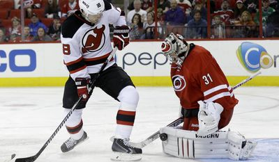 Carolina Hurricanes goalie Anton Khudobin (31), of Kazakhstan, blocks New Jersey Devils' Steve Bernier (18) during the first period of an NHL hockey game in Raleigh, N.C., Saturday, April 5, 2014. (AP Photo/Gerry Broome)