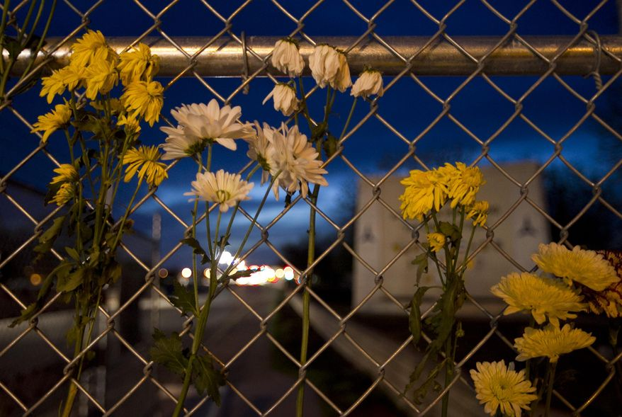 """Flowers hang at the East Gate of the army base at Fort Hood, Texas, on Friday, April 4, 2014, in honor of the victims of Wednesday's shooting. The Fort Hood soldier who gunned down three other military men before killing himself had an argument with colleagues in his unit before opening fire, and investigators believe his mental condition was not the """"direct precipitating factor"""" in the shooting, authorities said Friday. (AP Photo/Austin American-Statesman, Jay Janner)"""