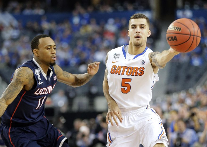 Florida guard Scottie Wilbekin (5) passes as Connecticut guard Ryan Boatright (11) defends during the first half of the NCAA Final Four tournament college basketball semifinal game Saturday, April 5, 2014, in Arlington, Texas. (AP Photo/Eric Gay)