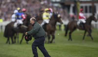 Starting tape is stretched across the course after a false start to the Grand National horse race at Aintree Racecourse Liverpool, England, Saturday, April 5, 2014. (AP Photo/Jon Super)