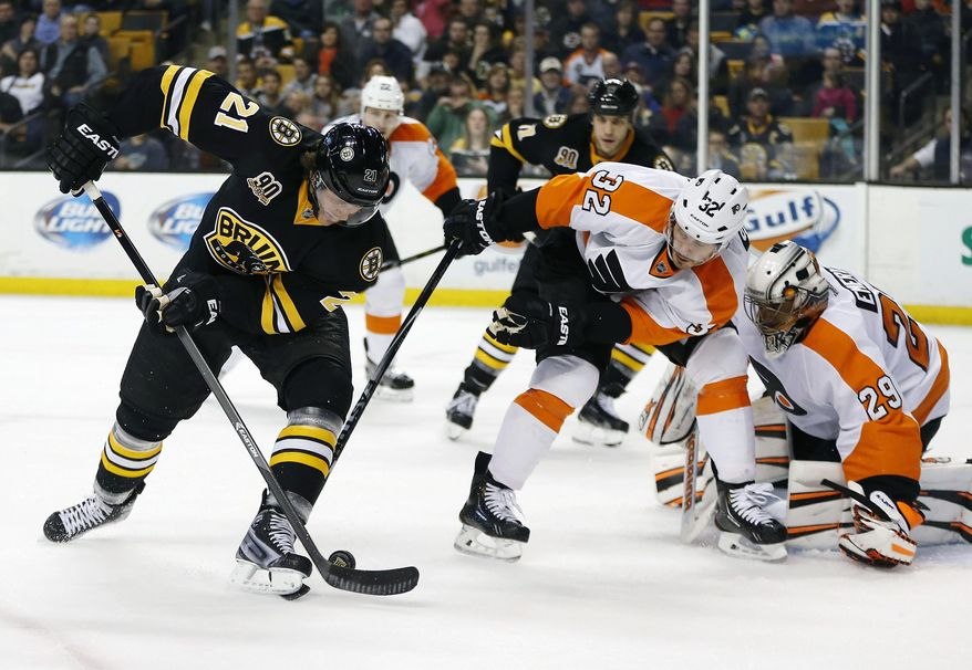 Boston Bruins' Loui Eriksson (21) tries to get a shot off against Philadelphia Flyers' Mark Streit (32) in the second period of an NHL hockey game in Boston, Saturday, April 5, 2014. (AP Photo/Michael Dwyer)