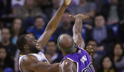 Golden State Warriors forward Draymond Green, left, shoots over Sacramento Kings forward Reggie Evans during the first half of an NBA basketball game Friday, April 4, 2014, in Oakland, Calif. (AP Photo/Marcio Jose Sanchez)